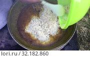 Купить «Uzbek pilaff cooking, pouring rice into cauldron with boiled meet, carrot and other ingredients», видеоролик № 32182860, снято 2 июня 2019 г. (c) Кекяляйнен Андрей / Фотобанк Лори