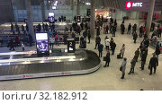 Купить «Arrived passengers are expected luggage in baggage delivery zone. Arrival lounge of the Pulkovo International airport. It serves citizens of St. Petersburg city», видеоролик № 32182912, снято 2 апреля 2019 г. (c) Кекяляйнен Андрей / Фотобанк Лори