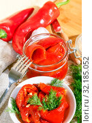 Homemade summer crop preservation, vegetable vegetarian diet wholesome food, natural red bell fried pepper with garlic marinated in a glass jar and a white plate on the table. Стоковое фото, фотограф Светлана Евграфова / Фотобанк Лори