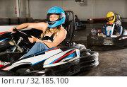 Купить «Female racer in helmet driving kart on track», фото № 32185100, снято 19 октября 2019 г. (c) Яков Филимонов / Фотобанк Лори