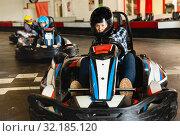 Купить «Female racer in helmet driving kart on track», фото № 32185120, снято 18 марта 2019 г. (c) Яков Филимонов / Фотобанк Лори