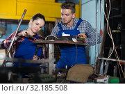 Купить «Glad man training female to repairing drill», фото № 32185508, снято 10 октября 2017 г. (c) Яков Филимонов / Фотобанк Лори