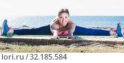 Купить «Female stretching for split on the beach», фото № 32185584, снято 6 мая 2017 г. (c) Яков Филимонов / Фотобанк Лори