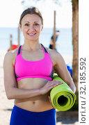 Купить «Woman standing with gymnastic mat», фото № 32185592, снято 6 мая 2017 г. (c) Яков Филимонов / Фотобанк Лори