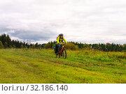 Купить «Cyclist traveler rides through the natural landscape», фото № 32186140, снято 3 сентября 2019 г. (c) Евгений Харитонов / Фотобанк Лори