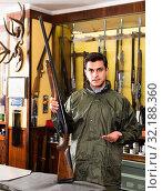 Купить «Confident hunter male wearing windbreaker in hunting shop with rifle in hands», фото № 32188360, снято 11 декабря 2017 г. (c) Яков Филимонов / Фотобанк Лори