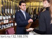 Купить «Male seller in gun shop showing rifle to woman client», фото № 32188376, снято 11 декабря 2017 г. (c) Яков Филимонов / Фотобанк Лори