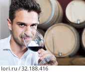 Man customer holding glass of red wine in winery section. Стоковое фото, фотограф Яков Филимонов / Фотобанк Лори