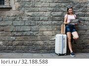 Купить «traveler with suitcase leaning against stone wall», фото № 32188588, снято 17 августа 2017 г. (c) Яков Филимонов / Фотобанк Лори