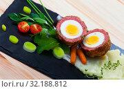 Купить «Dishes of traditional Scottish cuisine of scotch egg served with greens and potatoes», фото № 32188812, снято 6 июня 2020 г. (c) Яков Филимонов / Фотобанк Лори