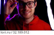 Купить «portrait of man in glasses over neon lights», видеоролик № 32189012, снято 15 октября 2019 г. (c) Syda Productions / Фотобанк Лори