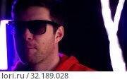 Купить «man in sunglasses dancing over neon lights», видеоролик № 32189028, снято 15 октября 2019 г. (c) Syda Productions / Фотобанк Лори
