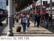 Люди идут по перрону Белорусского вокзала с пригородной электрички и поезда дальнего следования в городе Москве, Россия (2019 год). Редакционное фото, фотограф Николай Винокуров / Фотобанк Лори