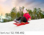 Купить «happy little girl sliding down on sled in winter», фото № 32198492, снято 10 февраля 2018 г. (c) Syda Productions / Фотобанк Лори