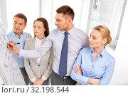 Купить «business team with scheme on flip chart at office», фото № 32198544, снято 5 апреля 2014 г. (c) Syda Productions / Фотобанк Лори