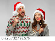 Купить «couple with christmas party props in ugly sweaters», фото № 32198576, снято 9 декабря 2018 г. (c) Syda Productions / Фотобанк Лори