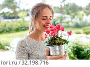Купить «young woman with cyclamen flowers at summer garden», фото № 32198716, снято 12 июля 2019 г. (c) Syda Productions / Фотобанк Лори