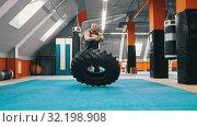 Купить «A man bodybuilder flips a tire on the floor over and over», видеоролик № 32198908, снято 21 сентября 2019 г. (c) Константин Шишкин / Фотобанк Лори