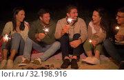 Купить «happy friends with sparklers at camp fire at night», видеоролик № 32198916, снято 9 сентября 2019 г. (c) Syda Productions / Фотобанк Лори