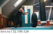 Купить «A tattooed man bodybuilder turning over the tire on the floor and moving it with this movement - powerlifting training», видеоролик № 32199124, снято 21 сентября 2019 г. (c) Константин Шишкин / Фотобанк Лори