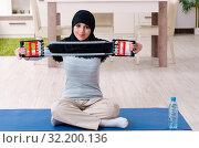 Купить «Young woman in hijab doing exercises at home», фото № 32200136, снято 18 марта 2019 г. (c) Elnur / Фотобанк Лори