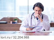 Купить «Young handsome doctor working in the clinic», фото № 32204988, снято 29 апреля 2019 г. (c) Elnur / Фотобанк Лори