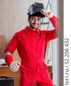 Young repairman with a welding gun electrode and a helmet weldin. Стоковое фото, фотограф Elnur / Фотобанк Лори