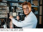 Купить «Strange engineer holds electric tube in laboratory», фото № 32207288, снято 17 июня 2019 г. (c) Tryapitsyn Sergiy / Фотобанк Лори