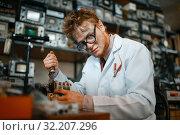 Купить «Strange scientist works with soldering iron in lab», фото № 32207296, снято 17 июня 2019 г. (c) Tryapitsyn Sergiy / Фотобанк Лори
