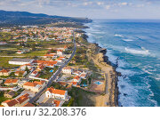 Купить «Aerial view of small town with red roofs on coastline Atlantic ocean. Top View of Azenhas Do Mar, Sintra, Portugal», фото № 32208376, снято 21 апреля 2019 г. (c) Кирилл Трифонов / Фотобанк Лори