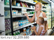Купить «Woman and girl picking fresh dairy products in refrigerated section», фото № 32209680, снято 19 октября 2019 г. (c) Яков Филимонов / Фотобанк Лори