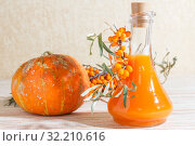 Vegetarian food, healthy nutrition, preserving the harvest of ripe juicy sea-buckthorn and home-made pumpkin, preparing fresh healthy vitamin drink and healing broth. Bottle of juice and branches of orange sea buckthorn. Стоковое фото, фотограф Светлана Евграфова / Фотобанк Лори