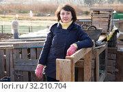 Купить «Farmer girl in the backyard of a village house», фото № 32210704, снято 15 ноября 2019 г. (c) Яков Филимонов / Фотобанк Лори