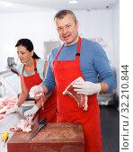 Купить «Sellers working in shop, man demonstrating meat», фото № 32210844, снято 22 июня 2018 г. (c) Яков Филимонов / Фотобанк Лори