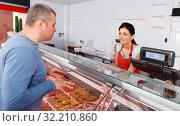 seller helping attentive customer choosing different sausages. Стоковое фото, фотограф Яков Филимонов / Фотобанк Лори