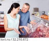Купить «Sad couple customers choosing meat in shop», фото № 32210872, снято 22 июня 2018 г. (c) Яков Филимонов / Фотобанк Лори