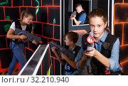 Jolly girl aiming laser gun at other players. Стоковое фото, фотограф Яков Филимонов / Фотобанк Лори