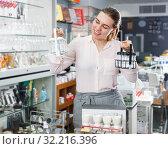 Купить «Smiling female consumer choosing set for salt and pepper», фото № 32216396, снято 2 мая 2018 г. (c) Яков Филимонов / Фотобанк Лори
