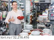 Купить «Young woman consumer ceramic plates in tableware shop», фото № 32216416, снято 2 мая 2018 г. (c) Яков Филимонов / Фотобанк Лори
