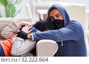 Купить «Armed man assaulting young woman at home», фото № 32222664, снято 15 декабря 2017 г. (c) Elnur / Фотобанк Лори