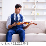 Купить «Young musician man practicing playing violin at home», фото № 32223048, снято 15 августа 2017 г. (c) Elnur / Фотобанк Лори