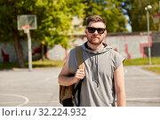 Купить «man with backpack at street basketball playground», фото № 32224932, снято 21 июля 2019 г. (c) Syda Productions / Фотобанк Лори
