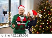 Купить «happy couple in christmas sweaters taking selfie», фото № 32225056, снято 9 декабря 2018 г. (c) Syda Productions / Фотобанк Лори