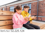 children with smartphones sitting on street bench. Стоковое фото, фотограф Syda Productions / Фотобанк Лори