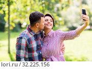 Купить «happy couple in park taking selfie by smartphone», фото № 32225156, снято 18 августа 2019 г. (c) Syda Productions / Фотобанк Лори