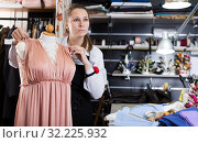 Portrait of woman designer who is thinking about new dress near mannequin. Стоковое фото, фотограф Яков Филимонов / Фотобанк Лори