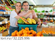 Купить «Cheerful family couple standing with full grocery cart after shopping», фото № 32225996, снято 27 апреля 2019 г. (c) Яков Филимонов / Фотобанк Лори