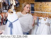 Купить «Woman choosing holiday dress for her daughter», фото № 32226048, снято 9 октября 2018 г. (c) Яков Филимонов / Фотобанк Лори