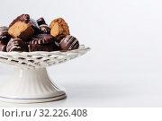 Купить «chocolate candy on plate on white table», фото № 32226408, снято 16 сентября 2019 г. (c) Майя Крученкова / Фотобанк Лори