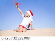 Купить «Счастливая девочка в колпаке Санта-Клауса сидит на песке на морском берегу и играет с красным игрушечным самолетиком», фото № 32228008, снято 30 июня 2019 г. (c) Лариса Капусткина / Фотобанк Лори